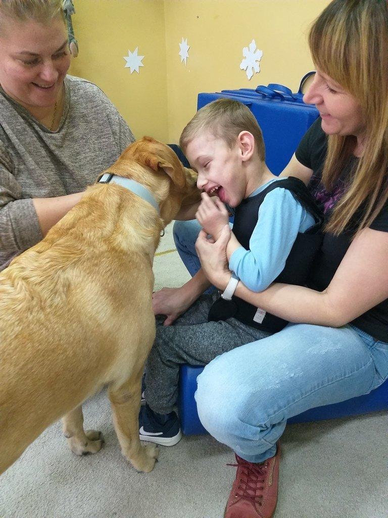 Na zdjęciu chłopiec - przytulający się do psa - zajęcia dog terapii