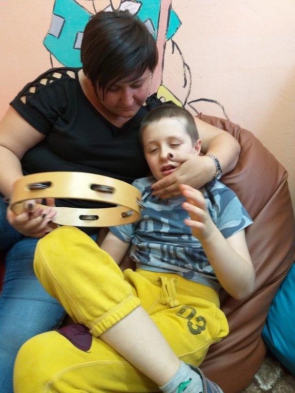 na zdjęciu chłopiec z Panią terapeutką - zabawa tamburynem