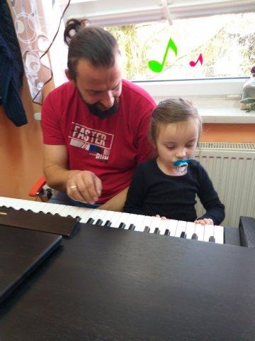 na zdjęciu muzykoterapeuta z dziewczynką przy pianinie