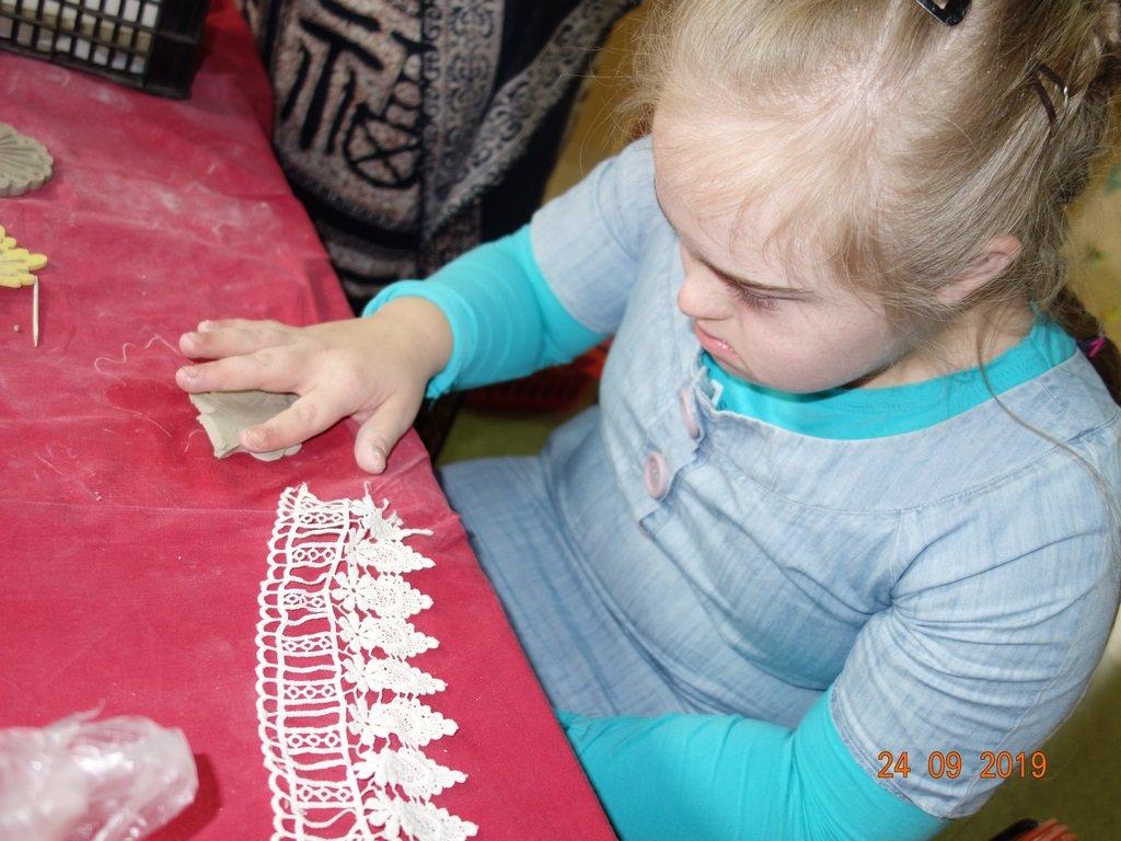 na zdjęciu dziewczynka na zajęciach terapii - lepienie z masy
