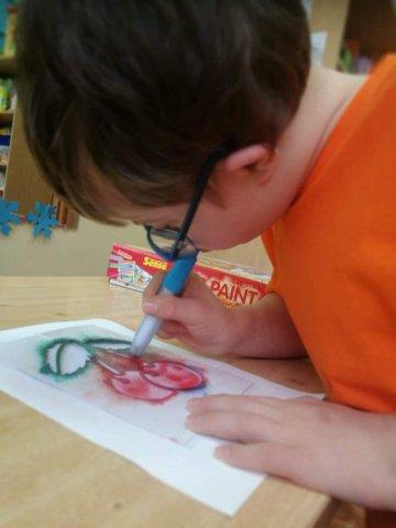 na zdjęciu chłopiec malujący pracę plastyczną