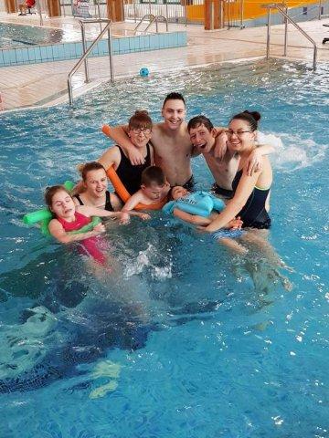 zajęcia na basenie - na zdjęciu grupa dzieci z paniami terapeutkami w basenie z hydromasażem